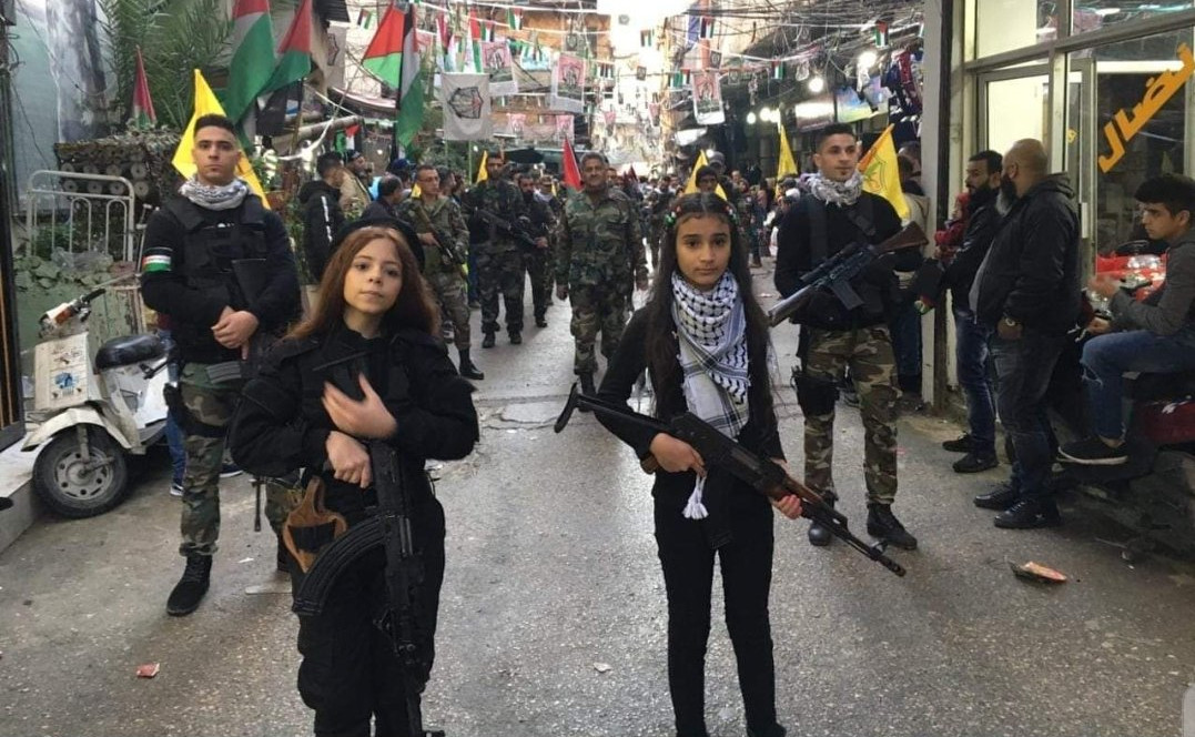 Palestinian girls bearing assault rifles in a military parade: Palestinian President Mahmoud Abbas' Fatah party posted this photo on its Facebook page. Defeat of Israel and hatred of Jews remains the focal point of Palestinian society, causing Palestinians to malign Israel even as Israel offers to help them defeat Covid-19. (Photo thanks to Palestinian Media Watch.)