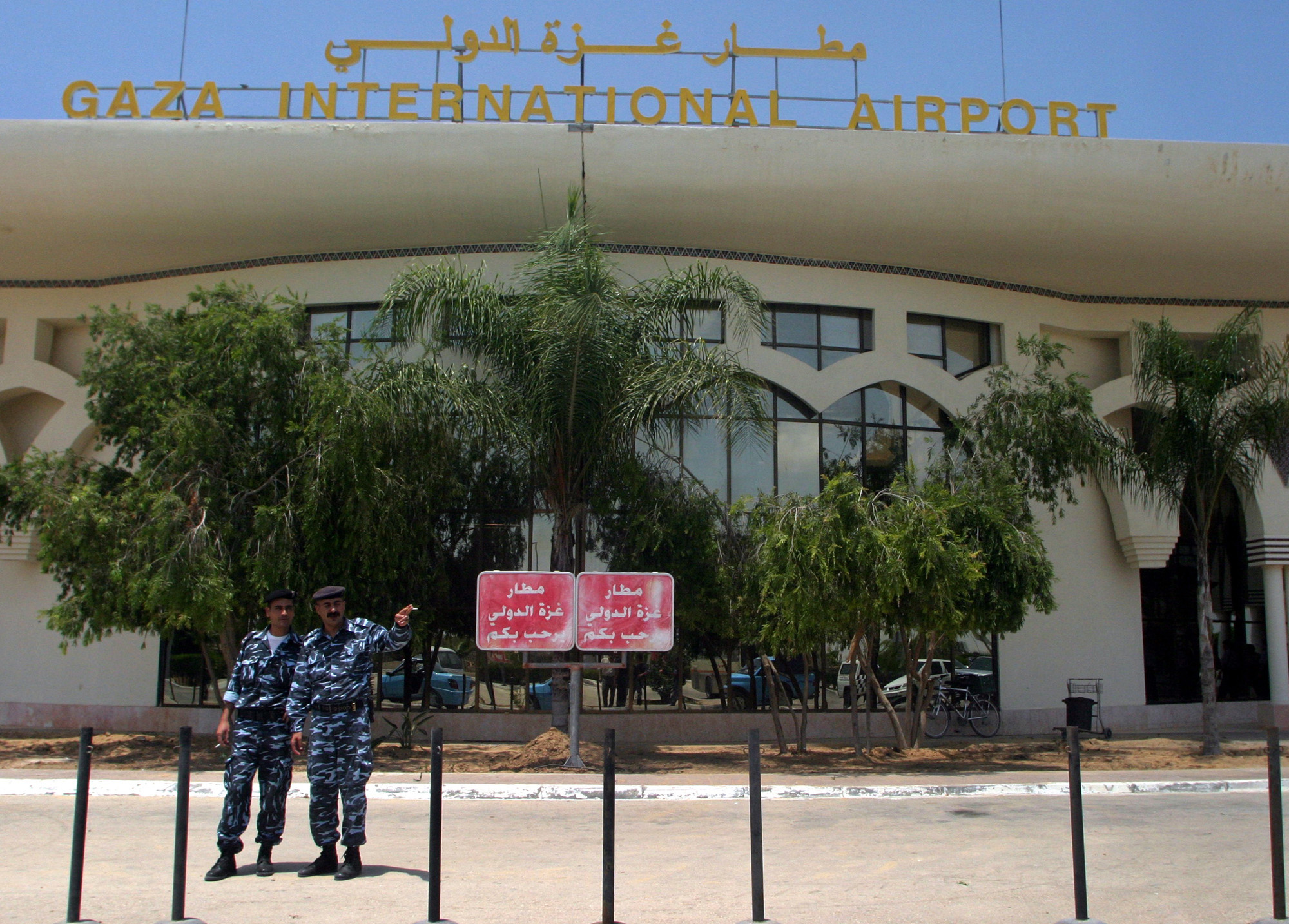 """A pair of lonely guards stand in front of the defunct Palestinian airport in Gaza. The equally defunct Palestine Airlines hasn't flown a flight in almost 20 years, but the corrupt Palestinian Authority budgets tens of millions every year for """"airline/airport operations."""""""