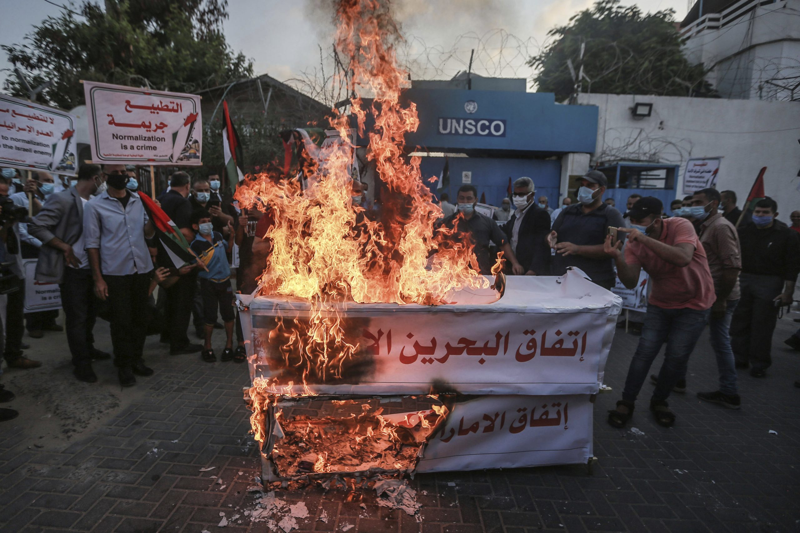 """Palestinians in Gaza protest peace between Arab states and Israel in front of the office of the UN Special Coordinator for the Middle East Peace Process (UNSCO). Signs say """"UAE and Bahrain agreement is occupation"""" and """"Normalization is betrayal."""" Palestinians are among the most vocal opponents of warming relations between Arabs and Jews."""