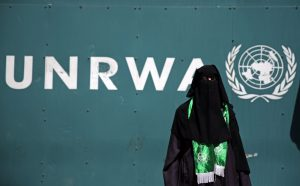 Palestinian woman wearing a green Hamas scarf protests potential U.S. cuts to funding for the United Nations Relief and Welfare Agency (UNRWA), which teaches Palestinian children the virtues of jihad and martyrdom in order to conquer Israel. (AP Photo/Khalil Hamra)